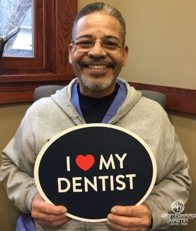 Patient holding a sign that says I love my dentist