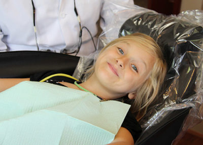 Young girl smiling in an exam chair