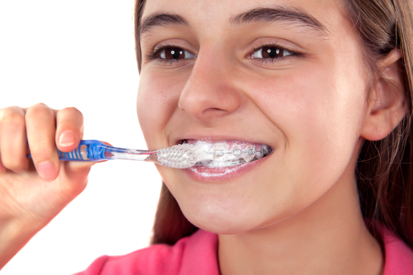 Girl brushing her teeth with braces