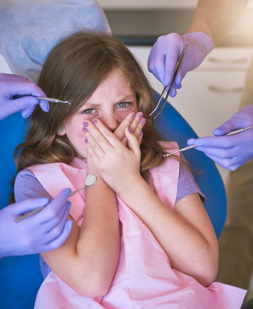 Young girl refusing dental exam