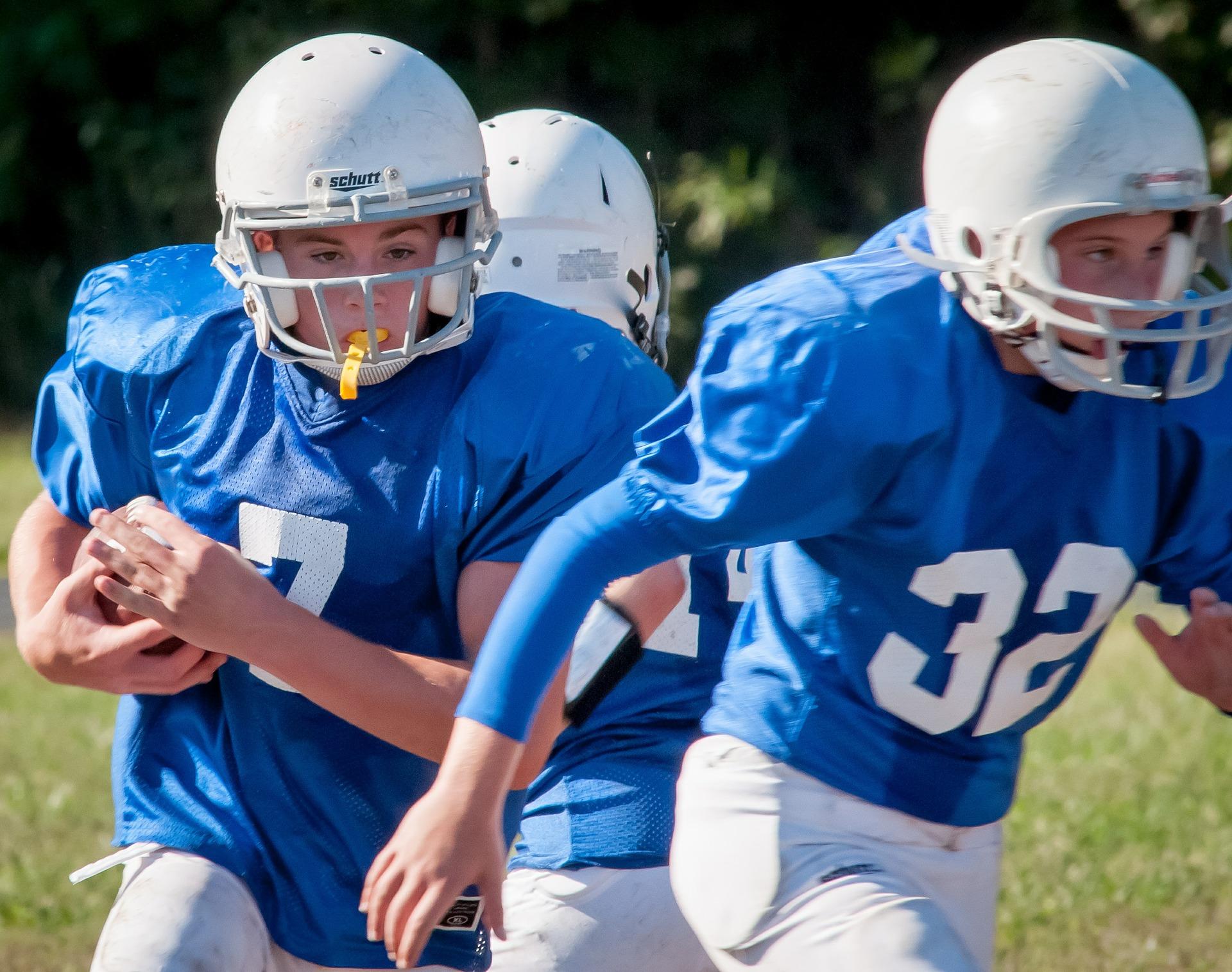 Young football players wearing blue jerseys playing football