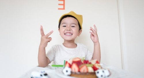 Child wearing a crown and smiling in front of a plate full of food