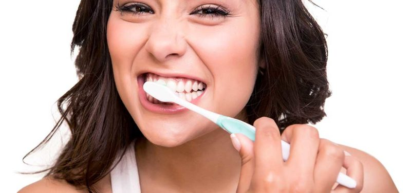 Young female brushing her teeth