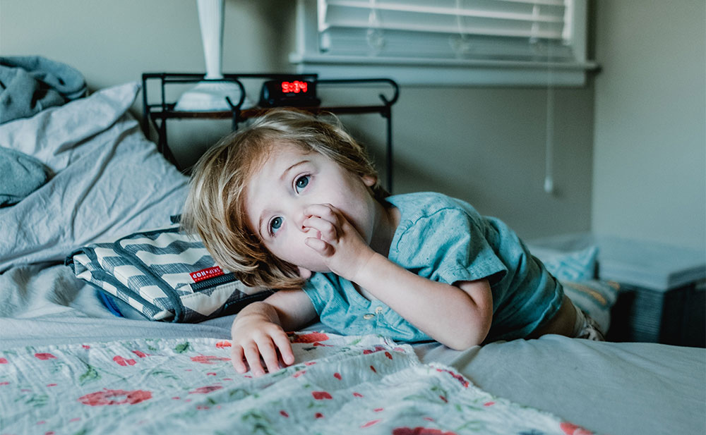 A child laying on a bed sucking their thumb