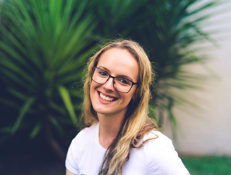 Blonde woman wearing a white shirt and black glasses smiling